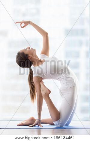 Young happy attractive woman practicing yoga, Camel exercise, Ustrasana pose, mudra, working out, wearing sportswear, white t-shirt, pants, indoor full length, near floor window with urban view
