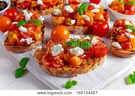 Tasty Traditional Tomato bruschetta with feta cheese topping, fresh basil