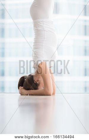 Closeup of Young woman practicing yoga, standing in salamba sirsasana exercise, headstand pose, working out, wearing white sportswear, indoor full length, near floor window with city view. Copy space