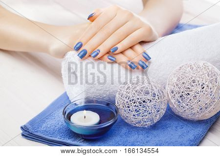 beautiful blue manicure with dekor and towel on the white wooden table. spa