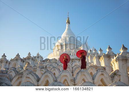 Asian monks sitting under umbrellas at historic temple Mingun Mandalay Myanmar