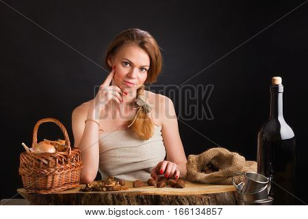 The young beautiful girl in a sundress from a canvas sits at an oak table about a basket with onions and garlic, dried mushrooms and chestnuts in a sacking