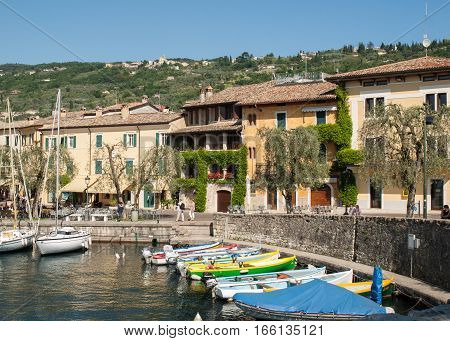 TORRI DEL BENACO, ITALY - MAY 4, 2016: Fishing boats in the small harbor of Torri del Benaco. Garda Lake. Italy
