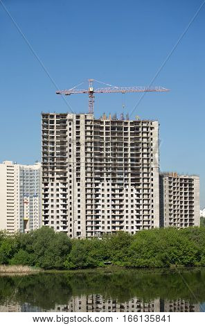 Long hoisting tower crane in construction new apartment building process over cloudless sky, vertical photo