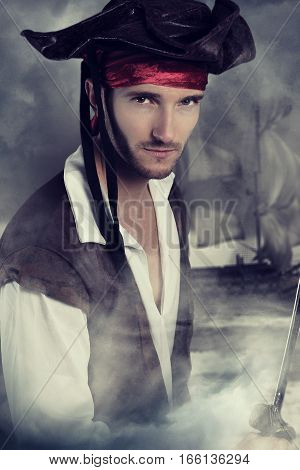 Young pirate holding a sword over a smoky background