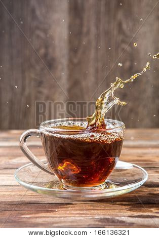 Photography of black tea in glass mug on saucer on brown background