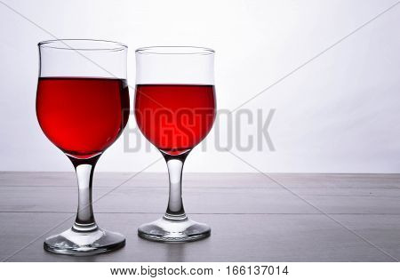 glass of red wine. Wine is poured into a glass from bottle on a light wooden background
