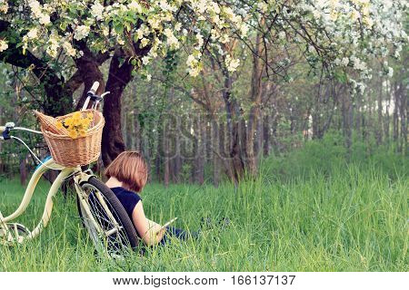 People who arrived on a bicycle resting reading a book in the park under a blossom tree / healthy lifestyle weekend