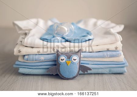 children's clothes with the diapers are stacked, and a toy bird owl