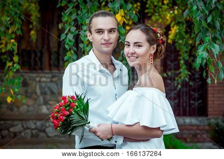 Happy loving wedding couple in the autumn park. Young handsome  groom embracing  his beautiful smiling bride in white dress, holding bouquet of red roses