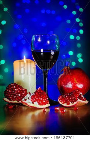 Glass of red wine, ripe pomegranate, and burning candle on the table with blurred green and blue lights on background