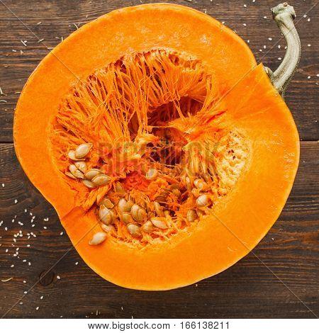 Round orange pumpkin half in cut. Close-up of fresh squash cutaway ready for preparing. Seasonal fruit healthy eating nutrition concept