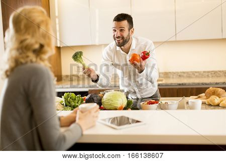Young Couple Preparing Meal In The Kitchen