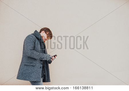 Stylish bearded man calling on the phone in the winter
