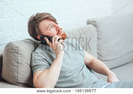 The bearded man sitting on the couch at home and calling the phone