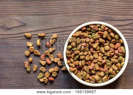 dry cat food in bowl on wooden background top view.