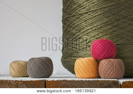 Large spool of thread and balls of color on the table