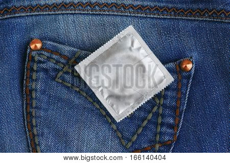Condom in the pocket of blue jeans. Safe sex concept.