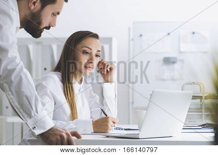 Portrait of a man and a woman in a white office. They are working at one laptop. He is leaning to her. She is looking at the screen and taking notes