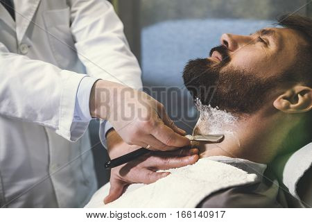Man Being Shaved Dangerously