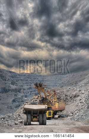 Heavy mining dump trucks are being loaded with iron ore on the opencast mining with stormy clouds on the background