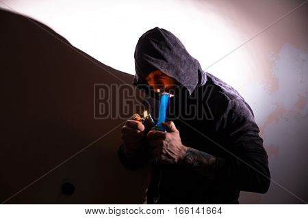Addictive man smoking marijuana bong with a shadow on the wall