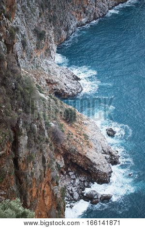 View from above of steep slopes with pine trees and rocky Mediterranean sea shore in Alanya Turkey