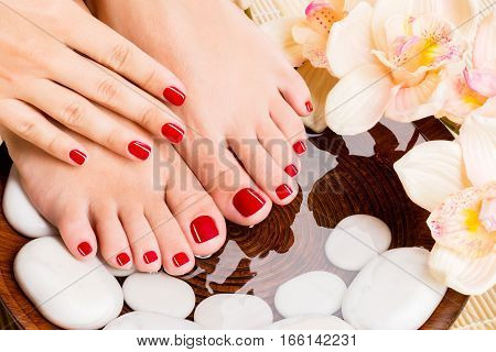 Manicured clean female feet and hands in spa wooden bowl with flowers and water closeup