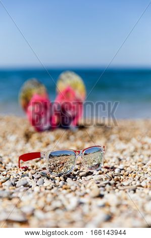 Photography of sunglasses on background slippers at seaside during day