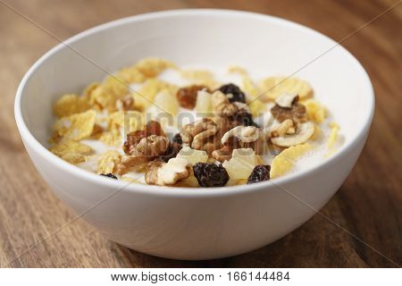 closeup photo of corn flakes with fruits and nuts in white bowl on wood table, simple healthy breakfast