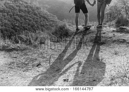 Black-and-white photo of the shadows mens on hill in afternoon