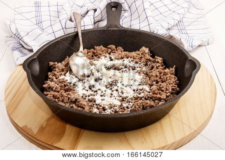 fried pork minced meat with flour in a cast iron pan