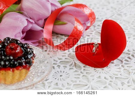 Golden engagement ring in a heart shaped box berries cake and a flower tulips