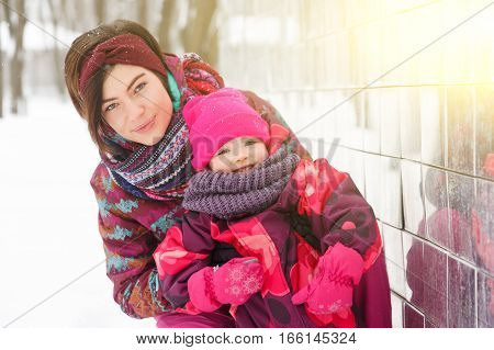 Photo of young woman with daughter in winter park near building