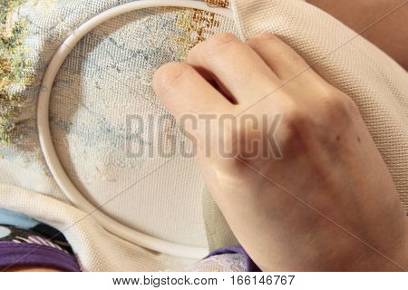 Woman sewing decoration picture on the white fabric