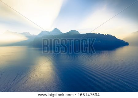 Grand game of light and shadow. Sunlight sat behind a mountain ridge. Rays of light pierce the sky. On water of the lake waves and light reflection .