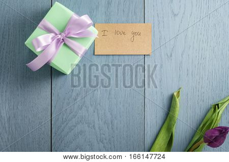 green gift box on blue wood table with paper card i love you, top view