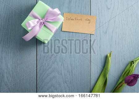 green gift box on blue wood table with paper card for valentines day, top view