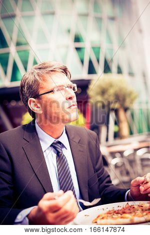 Mature businessman having lunch at an outdoors cafe.