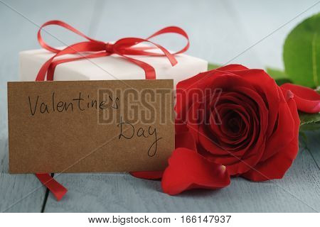 red rose on blue wood table with gift and valentines day paper card, shallow focus