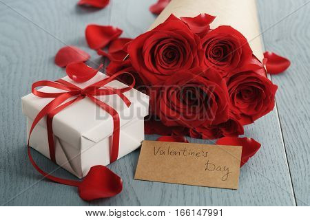 bouquet of red roses on blue wood table with gift and valentines day paper card, shallow focus