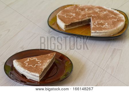 Piece of Christmas coffee cake with creamy souffle decorated star on beige wood.
