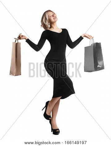 Shopping young woman holding bags isolated on white studio background. Love fashion and sales. Happy blond girl in black luxury glomour dress shopper with handbags and gifts.