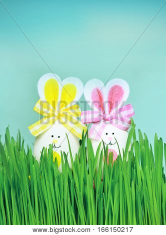 Colored easter eggs bunny on grass over blue background