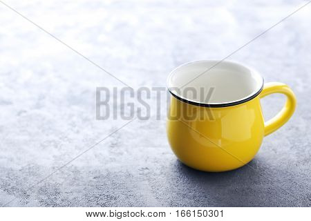 Yellow mug on a grey wooden table