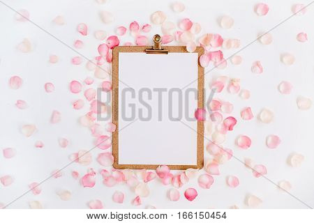 Clipboard mock up and pink rose petals pattern. Flat lay top view
