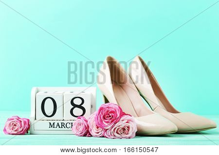 Pink Roses With Cube Calendar And High-heeled Shoes On Green Background