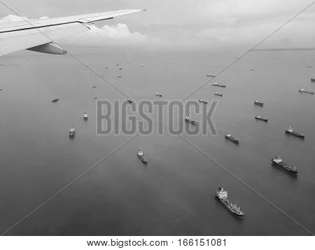 Many cargo ships float in the sea the view from the window of a plane black and white tone.