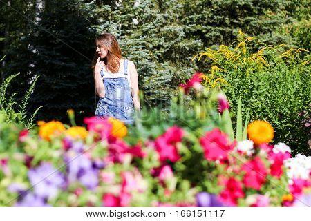 Young woman posing on the background, the foreground flowers.