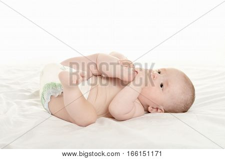 Adorable baby girl lying in pampers on blanket on a white background